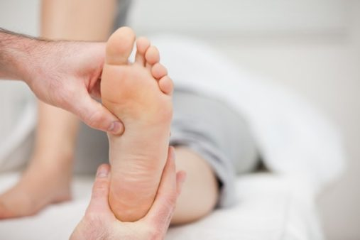 Massage therapist holding a foot