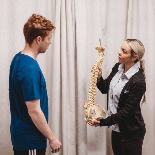 Physio demonstrating back pain to patient